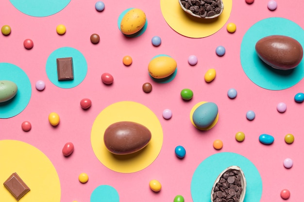 Ovos de páscoa inteiros e doces coloridos em fundo rosa Foto gratuita