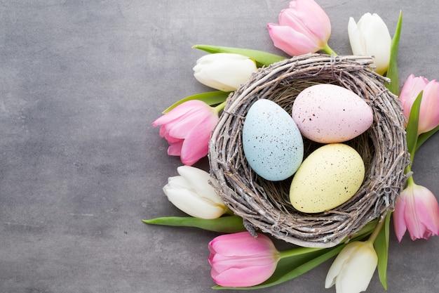Ovos de páscoa no ninho com tulipas ao redor Foto Premium