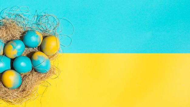 Ovos de páscoa no ninho grande na mesa brilhante Foto gratuita