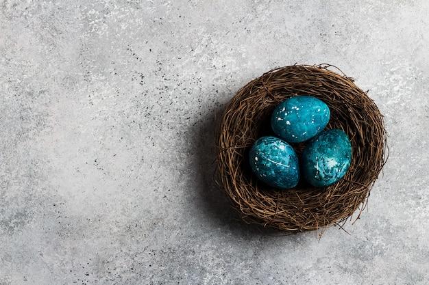 Ovos de páscoa no ninho pintado à mão em azul Foto gratuita