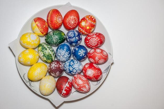 Ovos de páscoa no prato. pintado com cera e corantes alimentares. conceito de feriado de páscoa. resultado. Foto Premium