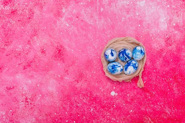 Ovos de páscoa pintados de azul no ninho Foto gratuita