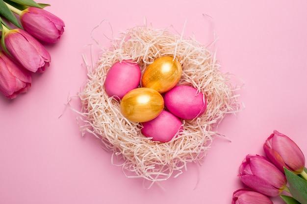 Ovos de páscoa rosa e ouro com flores em uma superfície rosa Foto Premium