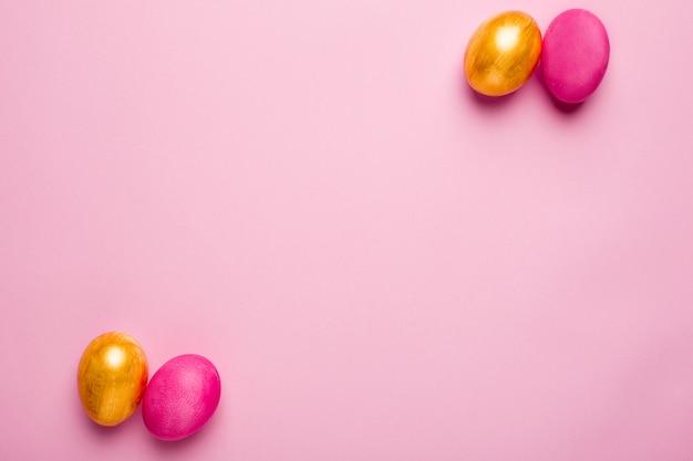 Ovos de páscoa rosa e ouro em uma superfície rosa Foto Premium