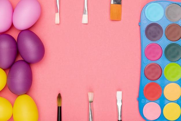 Ovos de vista superior e aquarela com pincéis para pintura Foto gratuita