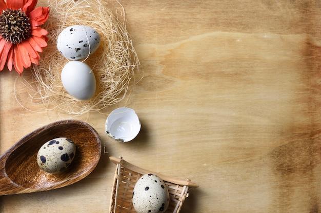 Ovos e flores de ninho no fundo de madeira. Foto Premium