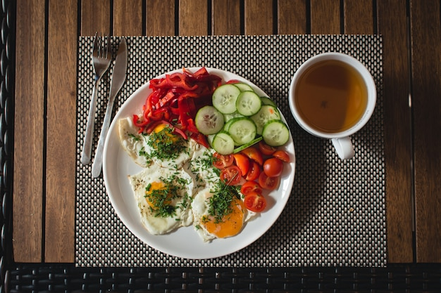 Ovos fritos com legumes e chá Foto gratuita