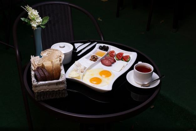 Ovos fritos com salsichas, azeitonas, queijo, pão e uma xícara de chá na mesa preta Foto gratuita