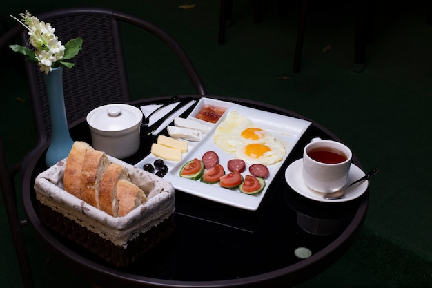 Ovos fritos com salsichas, azeitonas, queijo, pão e uma xícara de chá Foto gratuita