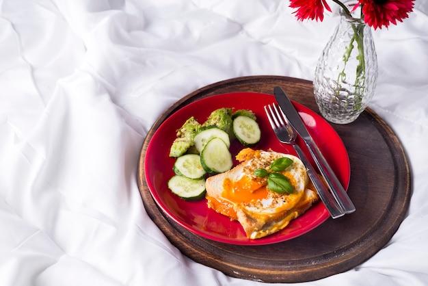 Ovos fritos com torradas e chá na cama Foto Premium