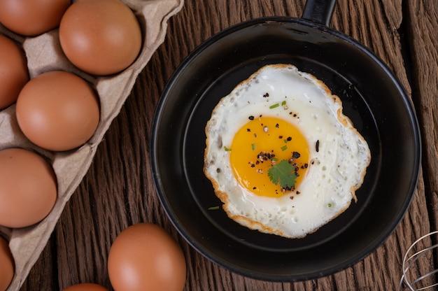 Ovos fritos em uma frigideira e ovos crus, alimentos orgânicos para uma boa saúde, ricos em proteínas Foto gratuita