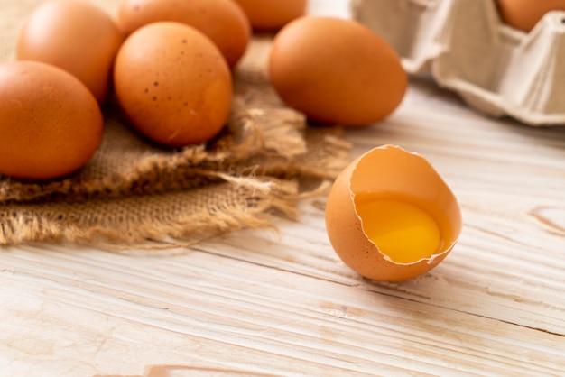 Ovos marrons com um quebrado e gema de ovo Foto Premium
