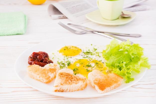 Ovos mexidos, pão frito, ketchup e alface folhas em um prato na mesa. café da manhã pronto para comer Foto Premium