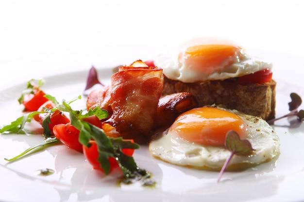 Ovos mexidos servidos com bacon e verde Foto gratuita
