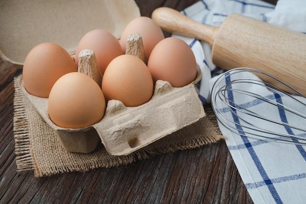 Ovos na caixa com batedor e rolo na mesa de madeira para cozinhar e conceito de padaria Foto Premium
