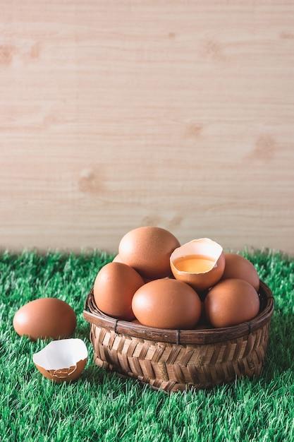 Ovos na cesta de madeira na grama verde. Foto Premium