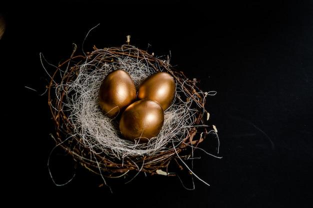 Ovos no ninho dos pássaros no fundo preto. feriado da páscoa Foto Premium