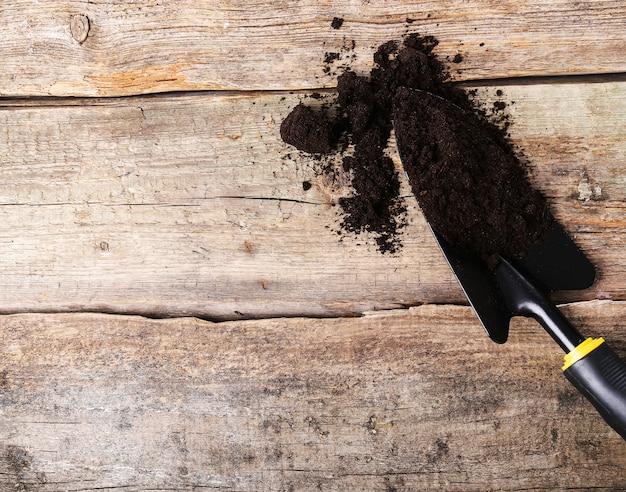 Pá com sujeira na mesa de madeira Foto gratuita