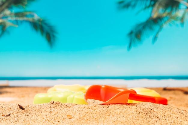 Pá de brinquedo na areia pelo mar Foto gratuita