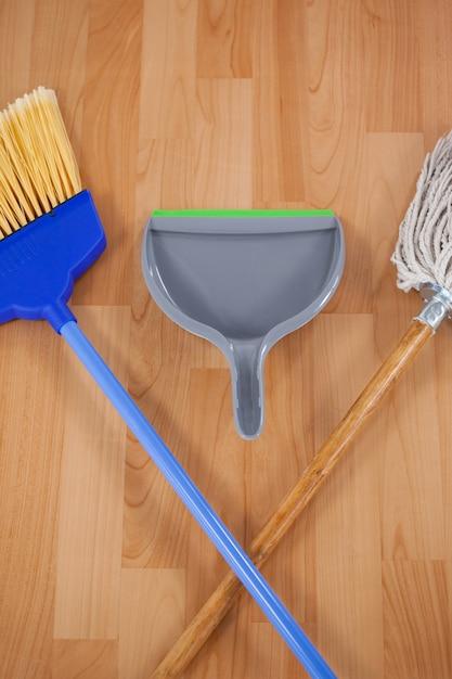 Pá de lixo, vassoura e esfregona no chão de madeira Foto Premium