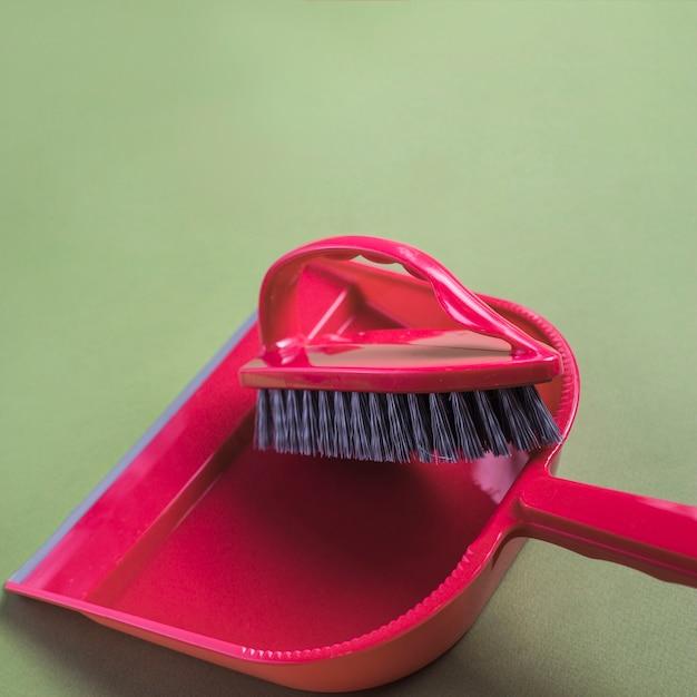 Pá de lixo vermelho e escova em fundo verde Foto gratuita