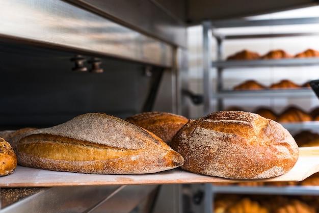 Pá de madeira com pão acabado de cozer do forno Foto gratuita
