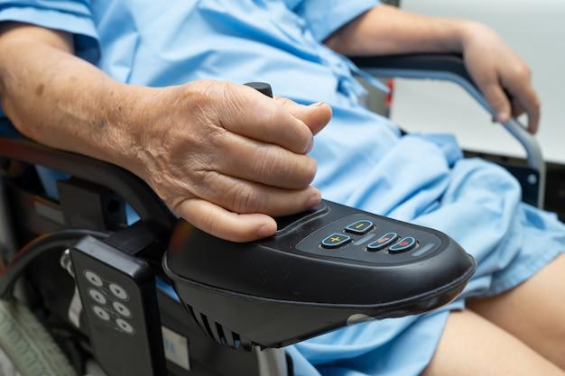 Paciente asiática sênior da mulher em uma cadeira de rodas elétrica. Foto Premium