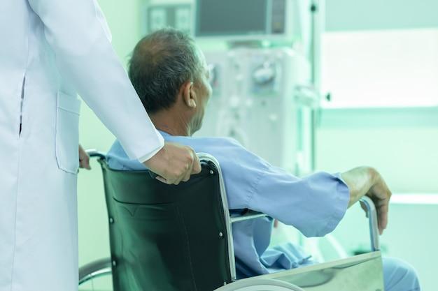 Paciente asiático na cadeira de rodas que senta-se no corredor do hospital com o doutor masculino asiático. Foto Premium