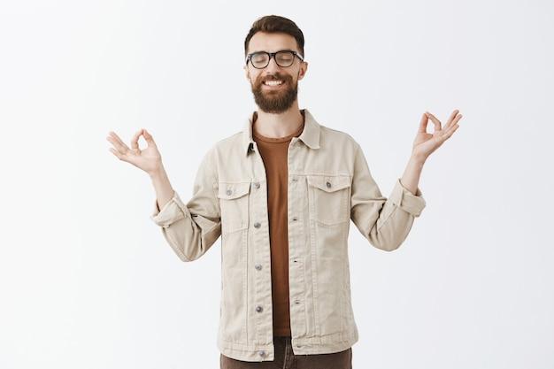 Paciente calmo homem barbudo de óculos posando contra a parede branca Foto gratuita