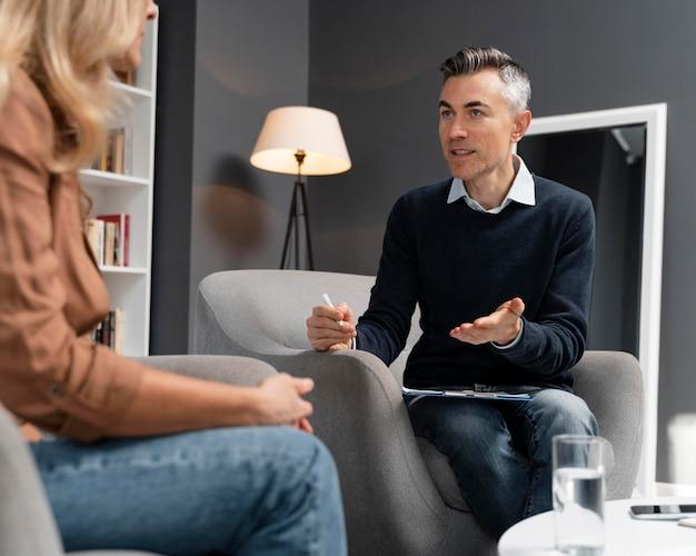 Paciente de meio tiro falando com terapeuta Foto gratuita