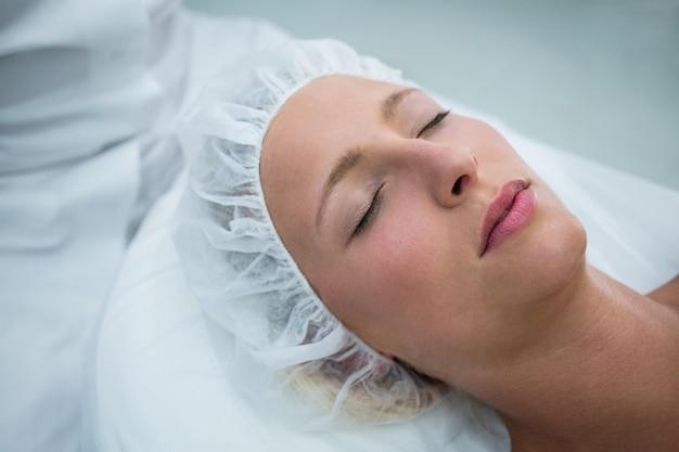 Paciente deitado na cama enquanto recebe tratamento cosmético Foto gratuita