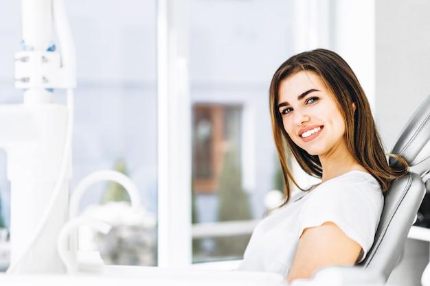 Paciente dental consideravelmente feliz e sorrindo que senta-se na cadeira dental no escritório dental. Foto Premium