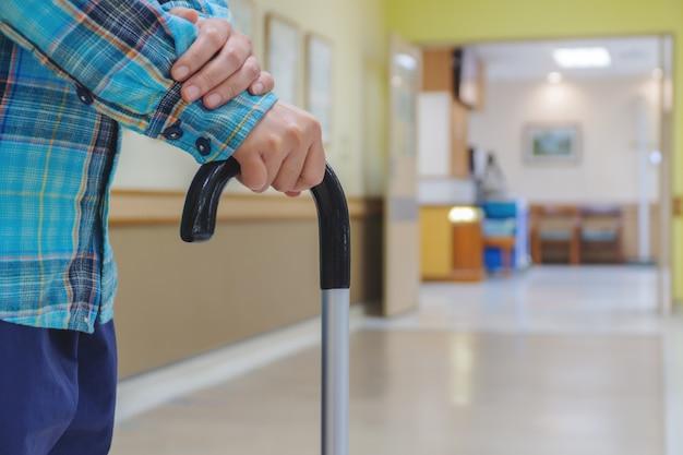 Paciente do sexo feminino estão treinando com bengalas no hospital. Foto Premium