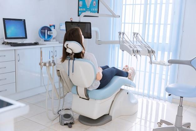 Paciente do sexo feminino jovem sentado na cadeira na clínica odontológica Foto gratuita
