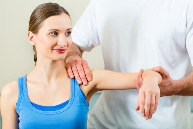 Paciente do sexo feminino na fisioterapia fazendo exercícios físicos com seu terapeuta, ele lhe dá uma massagem médica Foto Premium