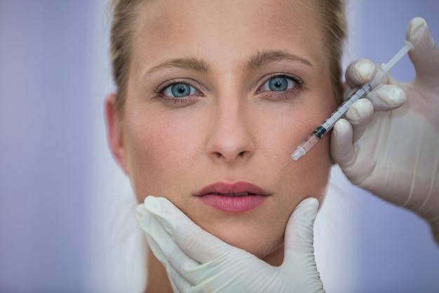 Paciente do sexo feminino recebendo uma injeção de botox no rosto Foto gratuita