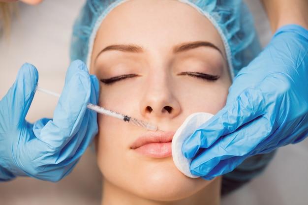 Paciente do sexo feminino recebendo uma injeção no rosto Foto gratuita
