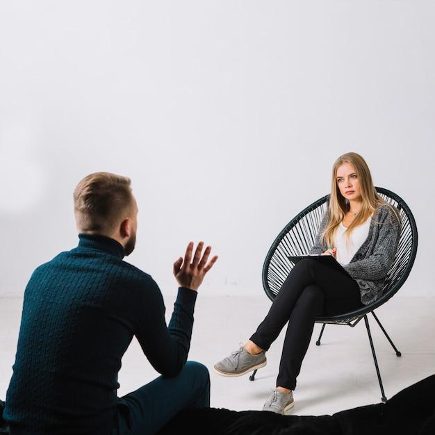 Paciente do sexo masculino falando com psicólogo feminino durante a terapia contra a parede branca Foto gratuita