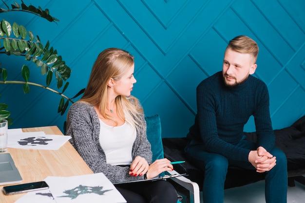 Paciente do sexo masculino falando com psicólogo feminino sentado com prancheta e caneta Foto gratuita