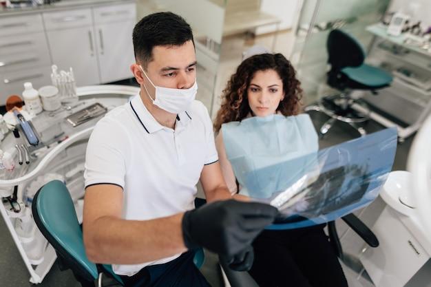 Paciente e dentista olhando para radiografia Foto gratuita