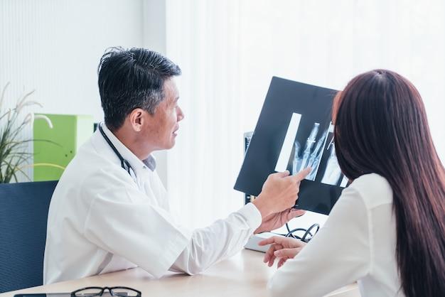 Paciente e médico asiático estão discutindo Foto Premium