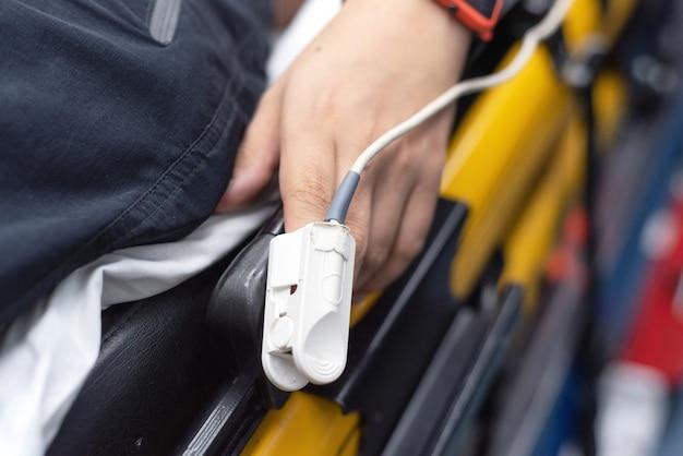 Paciente em ambulância usando o oxímetro de pulso de dedo, monitorando o sinal vital, conceito médico. Foto Premium
