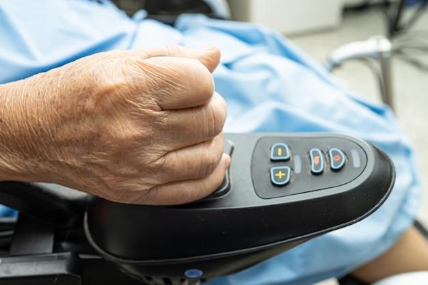 Paciente idosa ou idosa asiática em cadeira de rodas elétrica com controle remoto na enfermaria do hospital de enfermagem, conceito médico forte e saudável Foto Premium