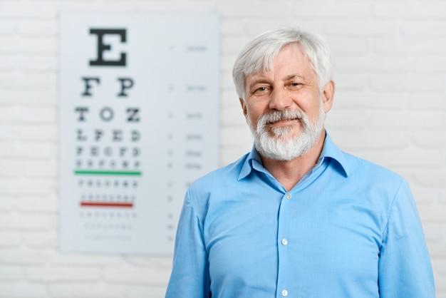 Paciente idoso que fica na frente da tabela visual da inspeção que pendura na parede branca no laboratório oftalmológico. Foto Premium
