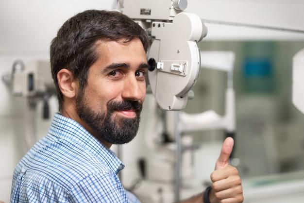 Paciente na clínica moderna de oftalmologia, verificando a visão do olho, aparecendo o polegar. Foto Premium