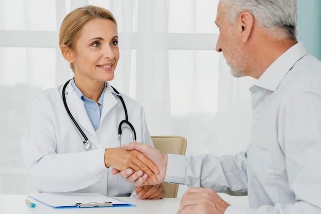 Paciente segurando a mão do médico Foto gratuita
