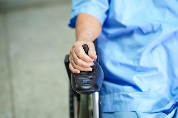 Paciente sênior asiático da mulher na cadeira de rodas elétrica com controle remoto. Foto Premium