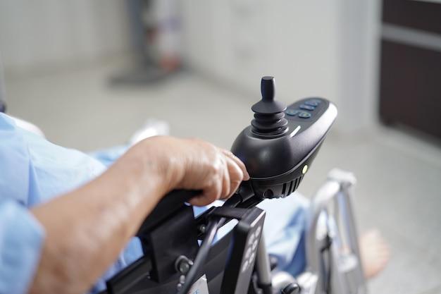 Paciente sênior asiático da mulher na cadeira de rodas elétrica. Foto Premium