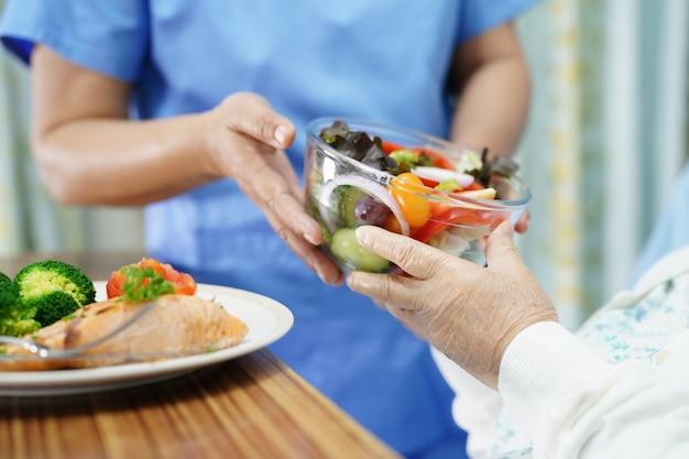 Paciente sênior asiático da mulher que come o café da manhã no hospital. Foto Premium