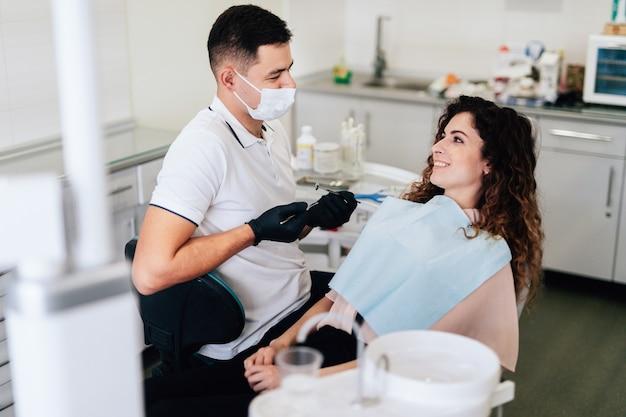 Paciente sorridente no consultório do dentista após o check-up Foto gratuita